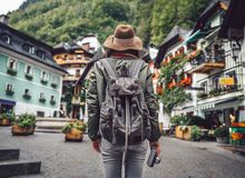 Young woman in a village. Young woman with a retro camera in an alpine village royalty free stock photography