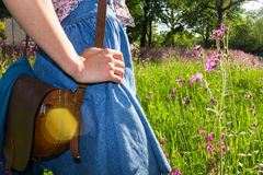 Young woman with vintage bag standing in field. Young woman enjoying a sunny day in a meadow Royalty Free Stock Images
