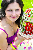 Young woman with vintage birdcage filled with red spring blossom Royalty Free Stock Images