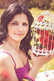 Young woman with vintage birdcage filled with spring blossom Stock Image