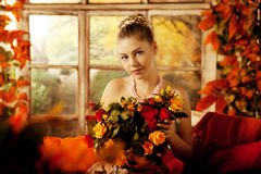 Young woman in vintage dress on autumn porch. Beauty girl in fa. Young beautiful woman in vintage dress on autumn porch. Beauty girl in fall orange leaves stock photography