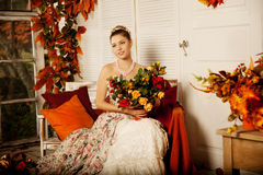 Young woman in vintage dress on autumn porch. Beauty girl in fa. Young beautiful woman in vintage dress on autumn porch. Beauty girl in fall orange leaves stock photo