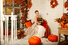 Young woman in vintage dress on autumn porch. Beauty girl in fa. Young beautiful woman in vintage dress on autumn porch. Beauty girl in fall orange leaves royalty free stock image