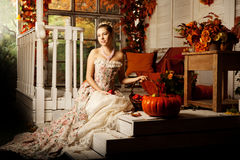Young woman in vintage dress on autumn porch. Beauty girl in fa. Young beautiful woman in vintage dress on autumn porch. Beauty girl in fall orange leaves stock image