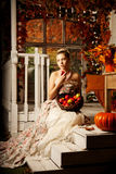 Young woman in vintage dress on autumn porch. Beauty  girl in fa Stock Photo