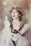 Young woman in vintage dress with plate full of chocolates Royalty Free Stock Photo