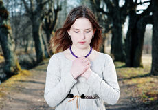 Young woman in vintage dress praying Stock Image