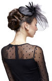 Young woman in vintage dress. And small female hat with veil. Shot from behind Royalty Free Stock Photos