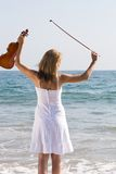 Young woman with violin on beach Stock Photo