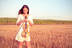 Young woman with violin outdoors. On the field in summer evening. Cross processing Royalty Free Stock Photos