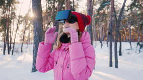 Young woman in virtual reality glasses. In the snow-covered forest, looking around: catching snowflakes stock footage