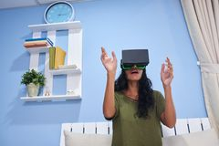 Experiencing virtual reality. Young woman in virtual reality headset playing video game Royalty Free Stock Image