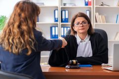Young woman visiting female lawyer. The young women visiting female lawyer stock image