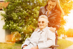 Young woman visiting grandmother in nursing home. Young women is visiting her grandmother in nursing home having a walk with here in a wheelchair Royalty Free Stock Photography