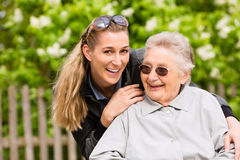 Young woman is visiting her grandmother in nursing home. Having a walk with here in a wheelchair Stock Images