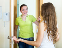 Young woman visiting her sister. Smiling women visiting her sister in her home Royalty Free Stock Photos