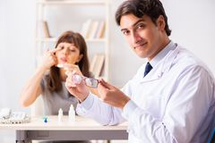 The young woman visiting male doctor ophthalmologist in hospital stock photography