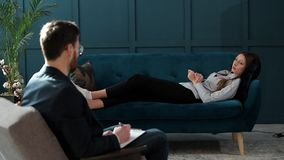 Young woman visiting male psychologist lying on the comfortable couch during psychological session in the luxury blue. Office interior stock footage