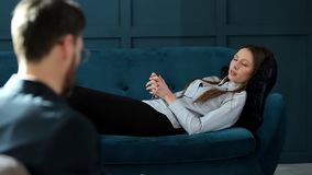 Young woman visiting male psychologist lying on the comfortable couch during psychological session in the luxury blue. Office interior stock video footage