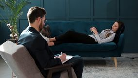 Young woman visiting male psychologist lying on the comfortable couch during psychological session in the luxury blue. Office interior stock video