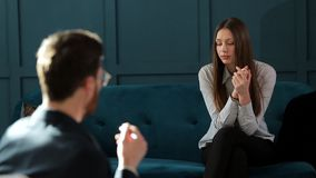 Young woman visiting male psychologist sitting on the comfortable couch during psychological session in the luxury blue. Office interior stock video footage