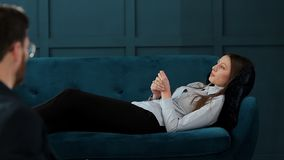 Young woman visiting male psychologist sitting on the comfortable couch during psychological session in the luxury blue. Office interior stock video