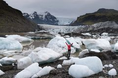 Young woman visiting nature landscape in Iceland glacier. Adventure woman by glacier nature on Iceland. Tourist in Icelandic by glacial lagoon / lake of Stock Photos