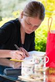 Young woman signing a guestbook. A young woman visitor signing a guestbook/journal outside on a glass table while visiting a friend royalty free stock photo