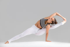 Young woman in Visvamitrasana pose, grey studio background. Young attractive woman practicing yoga, standing in Visvamitrasana pose, working out wearing Royalty Free Stock Images