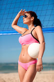 Young woman with volleyball ball and net on beach Stock Image