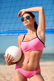 Young woman with volleyball ball and net on beach Royalty Free Stock Photography