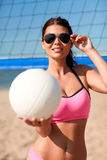 Young woman with volleyball ball and net on beach Stock Photo
