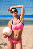 Young woman with volleyball ball and net on beach Royalty Free Stock Images