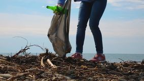 A young woman volunteer cleans the coastal area of debris. Environmental protection and responsibility. Eco and day of Earth conce