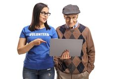 Young woman volunteering and showing an elderly man a laptop. Young women volunteering and showing an elderly men a laptop isolated on white background royalty free stock photo