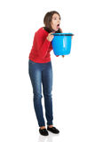Young woman vomiting to bucket. Royalty Free Stock Photography