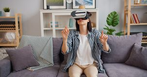 Young woman in vr glasses moving arms sitting on sofa in apartment stock footage
