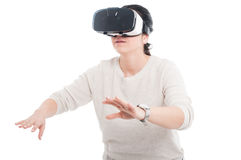 Young woman with VR headset touching something invisible Stock Images