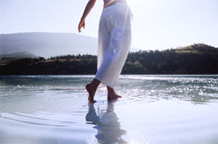 Young woman wading in lake.  royalty free stock images
