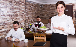Young woman waiter bringing order for visitors Stock Photography