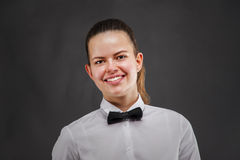 Young woman in waiter uniform over dark background. Royalty Free Stock Photo