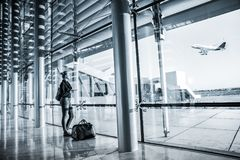 Young woman waiting at airport, looking through the gate window. Stock Photography