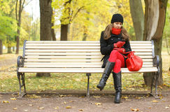 A young woman waiting on the bench in the park Stock Photo
