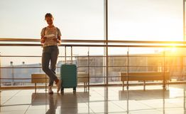 Young woman waiting for flying at airport at window with suitcas Stock Photos