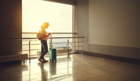 Young woman waiting for flying at airport at window with suitcas Stock Images