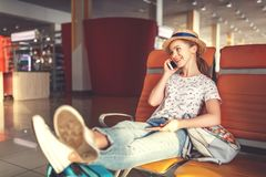 Young woman waiting for flying at airport at window with suitcas Royalty Free Stock Images