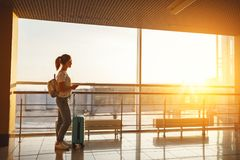 Young woman waiting for flying at airport at window with suitcas Royalty Free Stock Image