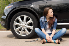 Young woman waiting for roadside assistance. For her car sitting cross legged in the road looking expectantly down the road with the wheel spanner lying Stock Images