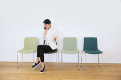 Young woman in waiting room talking on the phone Stock Photo