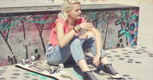 Young woman waiting at a skate park for a friend. Sitting against a low graffiti covered wall with her skateboard shielding her eyes from the hot summer sun stock footage